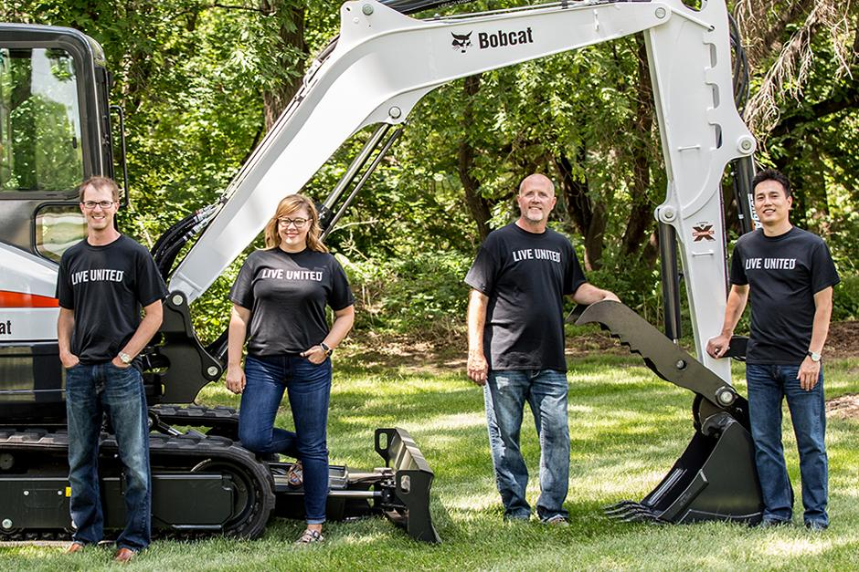 Bobcat Community Leadership Team Posing In Front Of A Bobcat Compact Excavator