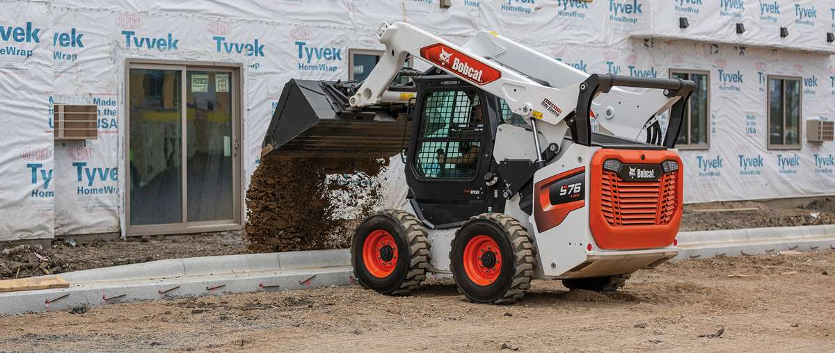 Bobcat T76 Compact Track Loader Hauling Rock With A Bucket Attachment