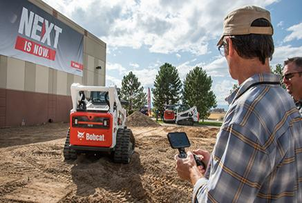Bobcat Equipment Operator Controlling Bobcat Compact Track Remotely In Front Of A Next Is Now Banner