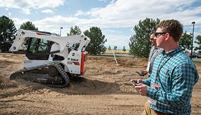 Bobcat Operator Using A Compact Track Loader Remotely With Phone