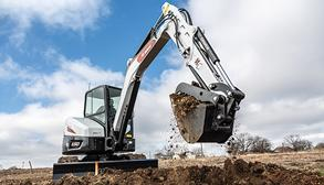 Contractor Removes A Bucketful Of Dirt From A Trench With A Bobcat Mini Excavator