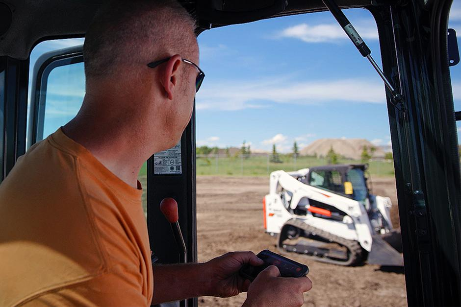 Man Operating A Bobcat Compact Track Loader From Inside The Cab Of Another Machine Using Bobcat MaxControl Remote Operation