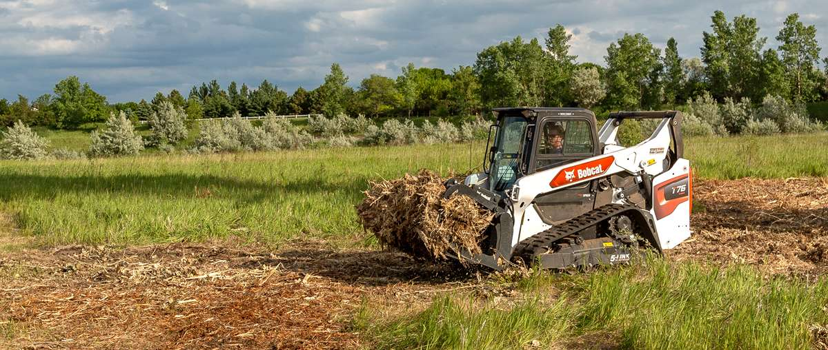Bobcat T76 Compact Track Loader In Open Field Hauling Debris With Root Grapple Attachment