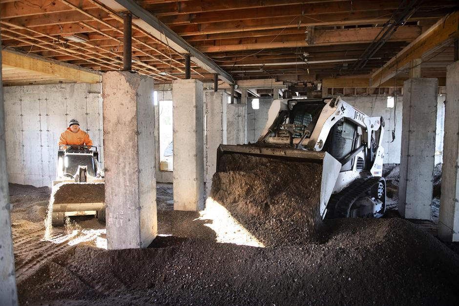 Operator Using A Bobcat T650 Compact Track Loader To Dump Soil In Building Foundation While A Second Operator Uses A Bobcat MT85 Mini Track Loader To Redistribute And Grade Dirt