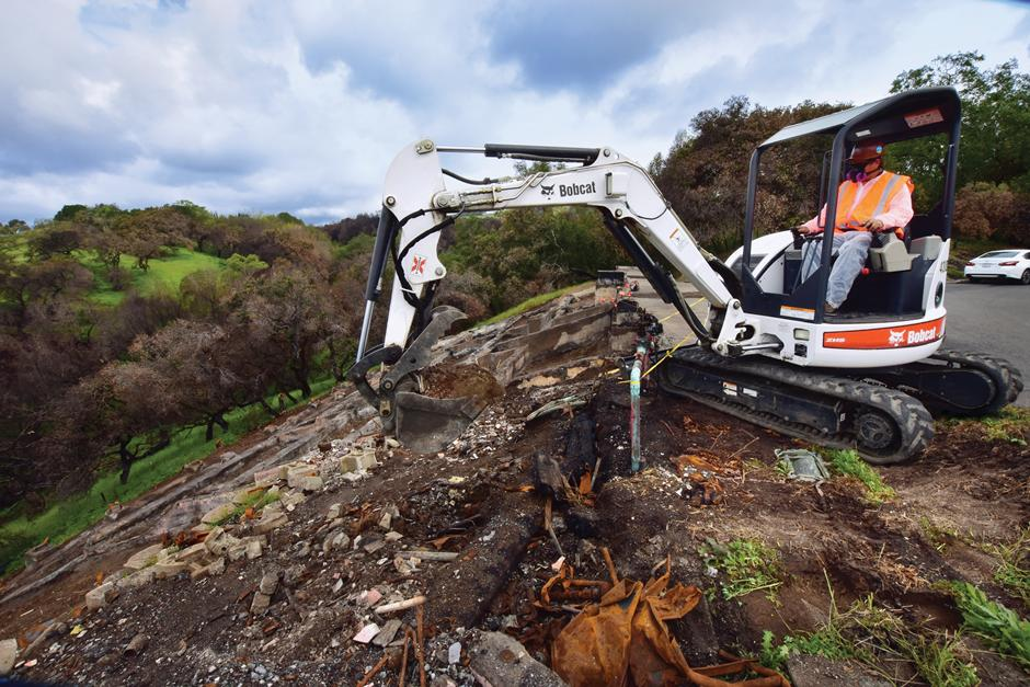 JM Environmental Employee Using Bobcat S650 Compact Excavator With Clamp Attachment To Clean Up Debris