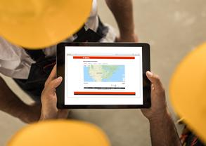 Construction workers reviewing Bobcat Machine IQ telematics on a digital tablet.