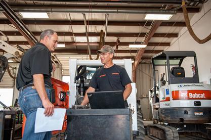 Two Bobcat service technicians stand near a Bobcat excavator.