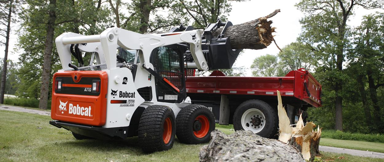Bobcat A770 All-Wheel Steer Loader lifts and carry heavy log