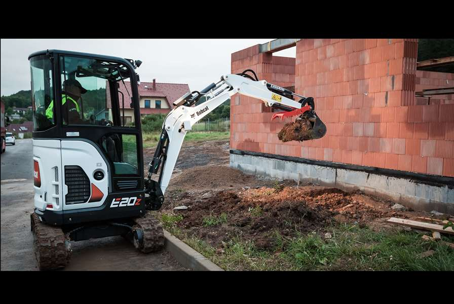 Bobcat E20z compact (mini) excavator with retractable undercarriage driving through small doorway.