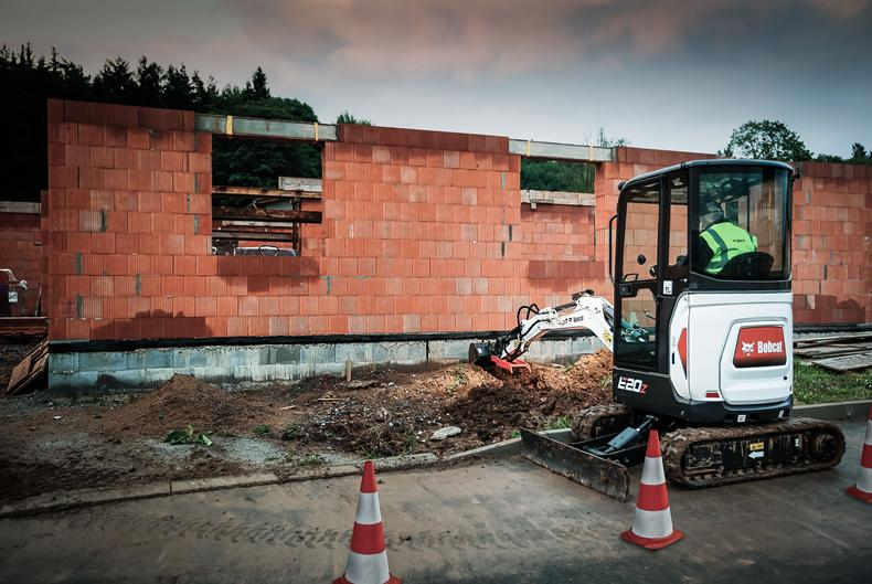 Bobcat E20z compact (mini) excavator with zero tail swing working in a barn.