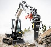Bobcat E26 compact excavator (mini excavator) digging with auger attachment.