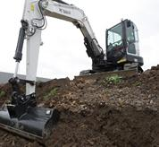 Bobcat compact excavators (mini excavators) digs in trench.