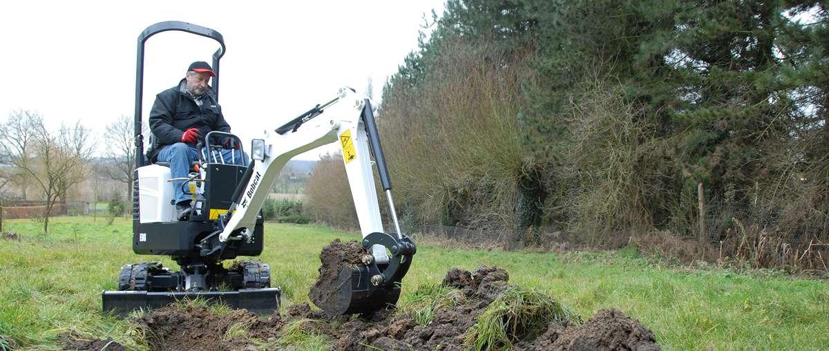 Escavatore compatto (miniescavatore) Bobcat E08 con benna in applicazione di paesaggistica