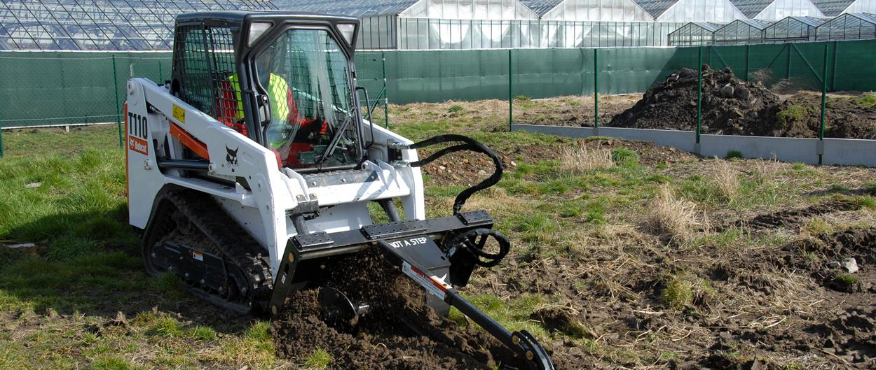 Bobcat T110 compact tracked loader with trencher on grass