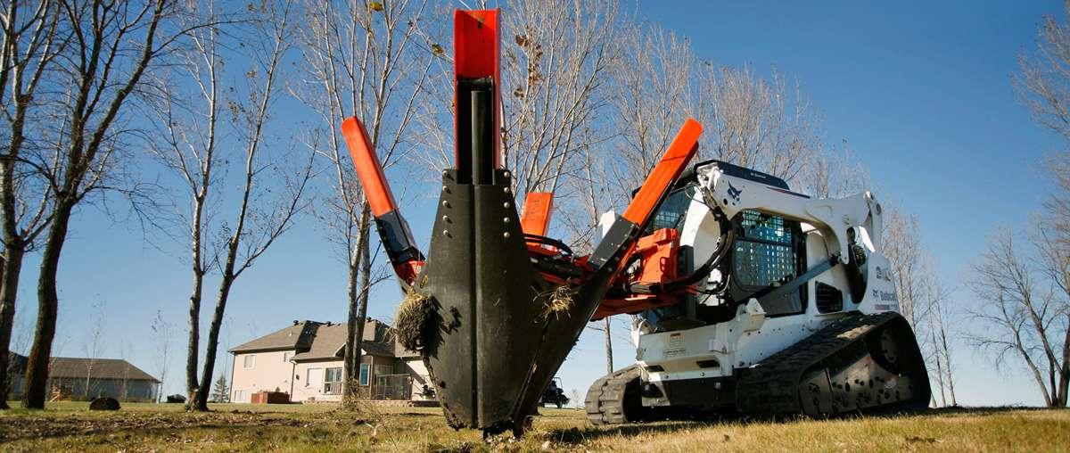 Компактный гусеничный погрузчик Bobcat T770 высаживает дерево при помощи пересадчика саженцев деревьев.