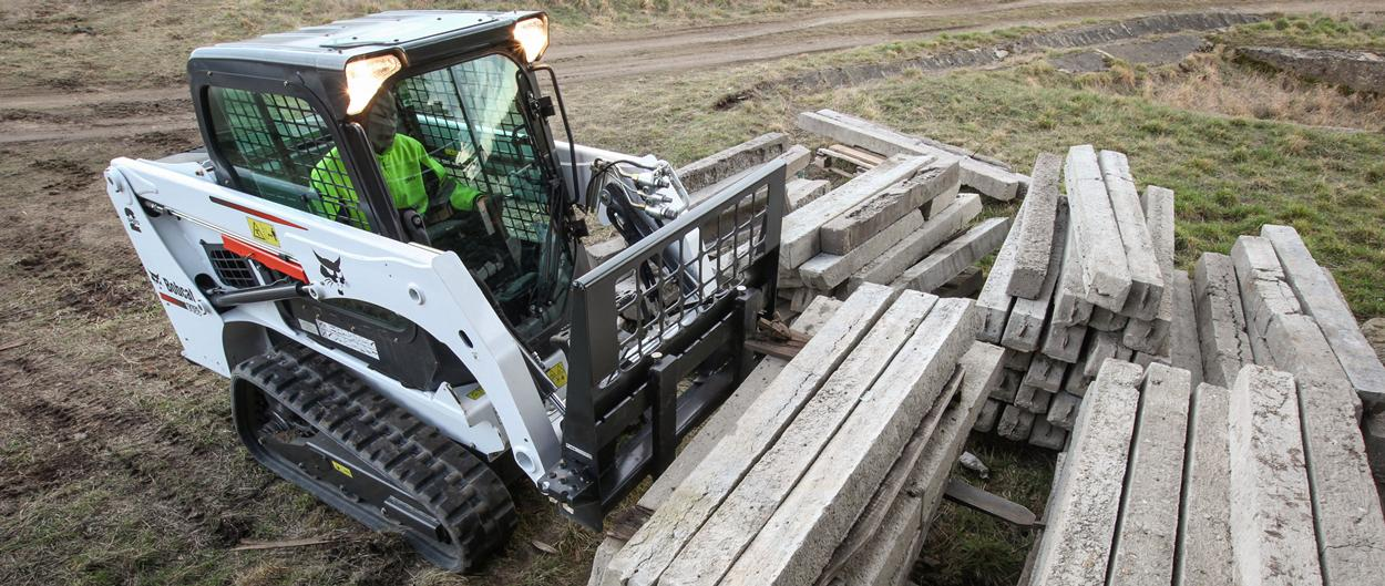 Bobcat T450 compact track loader with pallet forks, unloading a truck