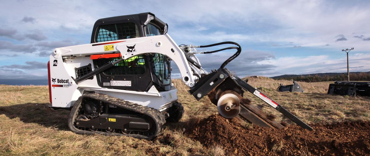 Bobcat T450 compact track loader carries a bucket of mulch in a residential garden.