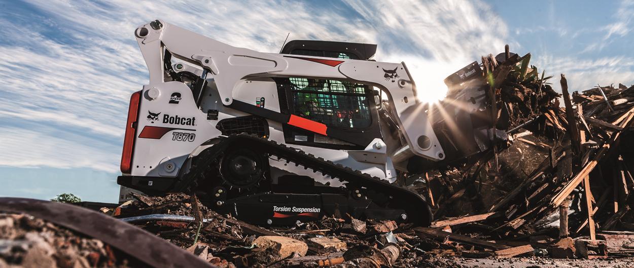 Bobcat T870 compacte rupslader met industrieel grijperaanbouwdeel.