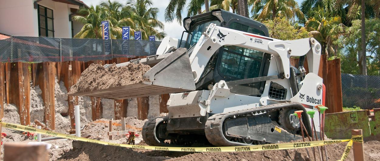 Bobcat T650 compact track loader dumps a load of black soil.
