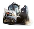 Bobcat T590 compact track loader backfills soil by house foundation.