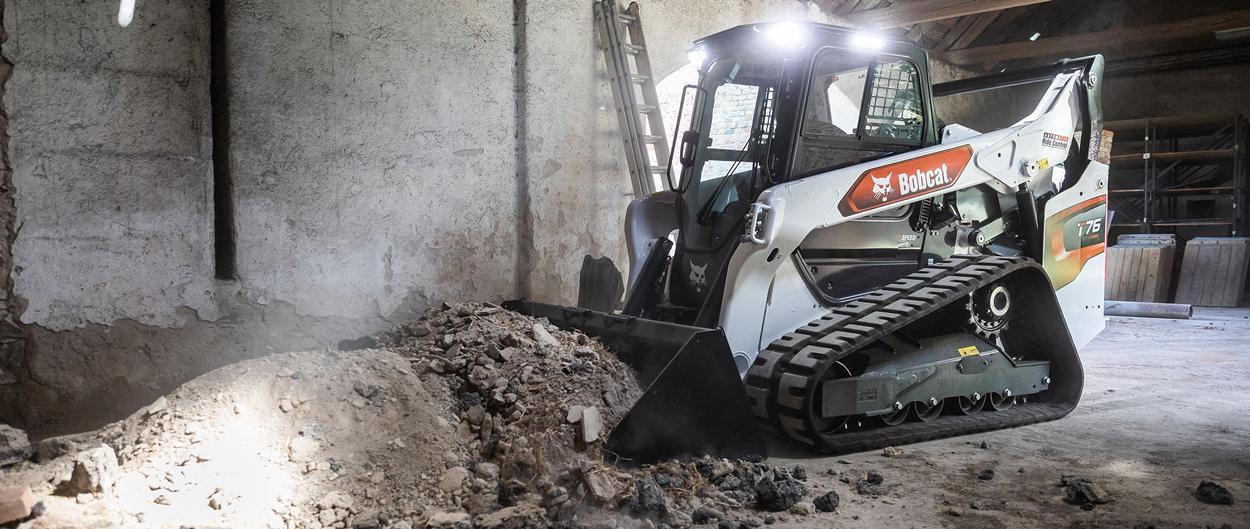 Bobcat T650 compact track loader dumps a load of black soil.