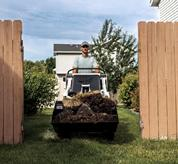 Bobcat mini track loader travels through fence gate.