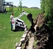 Ein Bobcat Mini-Raupenlader mit einem Erdbohrer als Anbaugerät legt ein Bodenloch an.