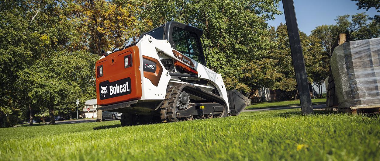 Bobcat T450 compact track loader with bucket in residential use.