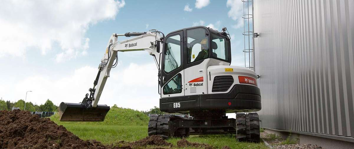 Bobcat R-Series E85 excavator using the clamp attachment to dig at a jobsite.