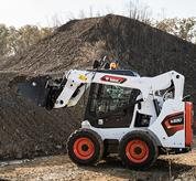 Bobcat skid-steer loader works in barn.