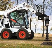 Bobcat skid steer loader with auger attachment digs hole.