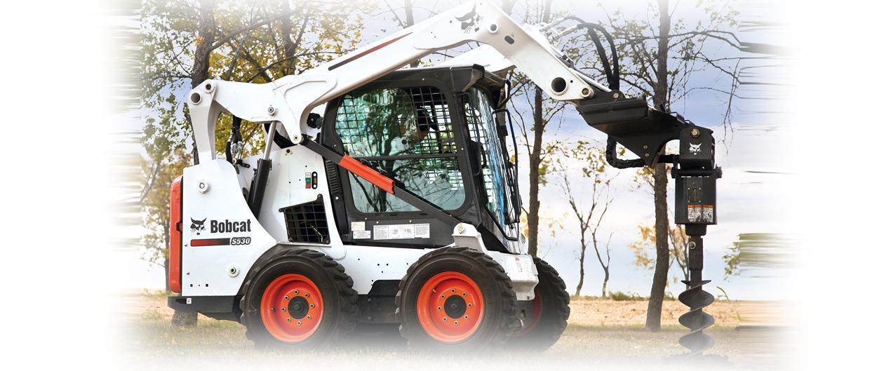 Bobcat S530 schranklader met aanbouwdeel grondboor aan het werk.