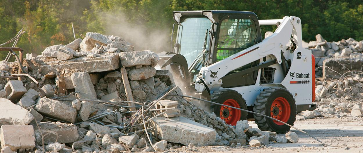 Bobcat S530 skid-steer loader with grapple attachment sorts debris.