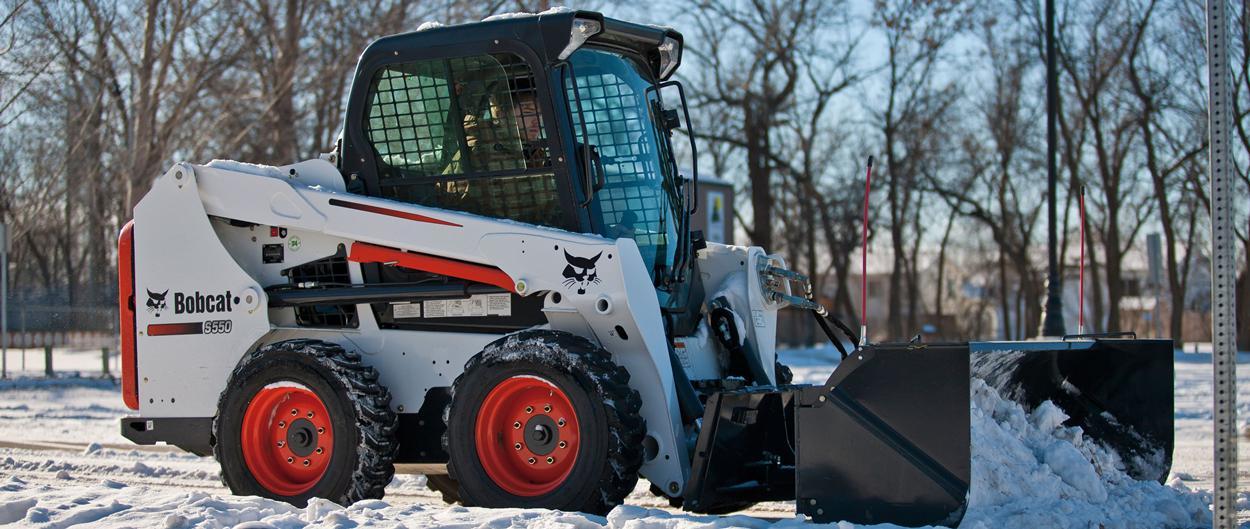 Ein mit einem Schneeschieber Schnee auf der Straße räumender Bobcat-Kompaktlader S550.