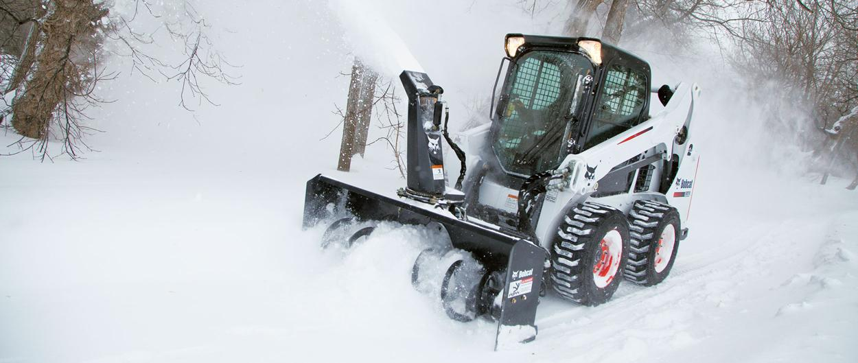 Bobcat S590 skid-steer loader dumps snow.