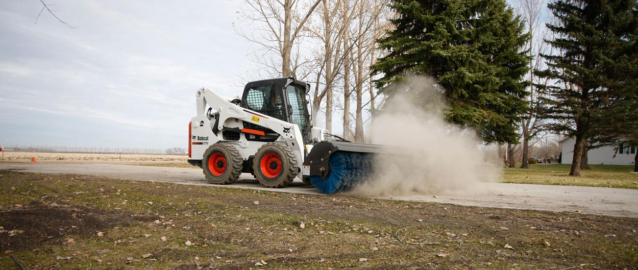 Bobcat S770 skid-steer loader with angle broom attachment.