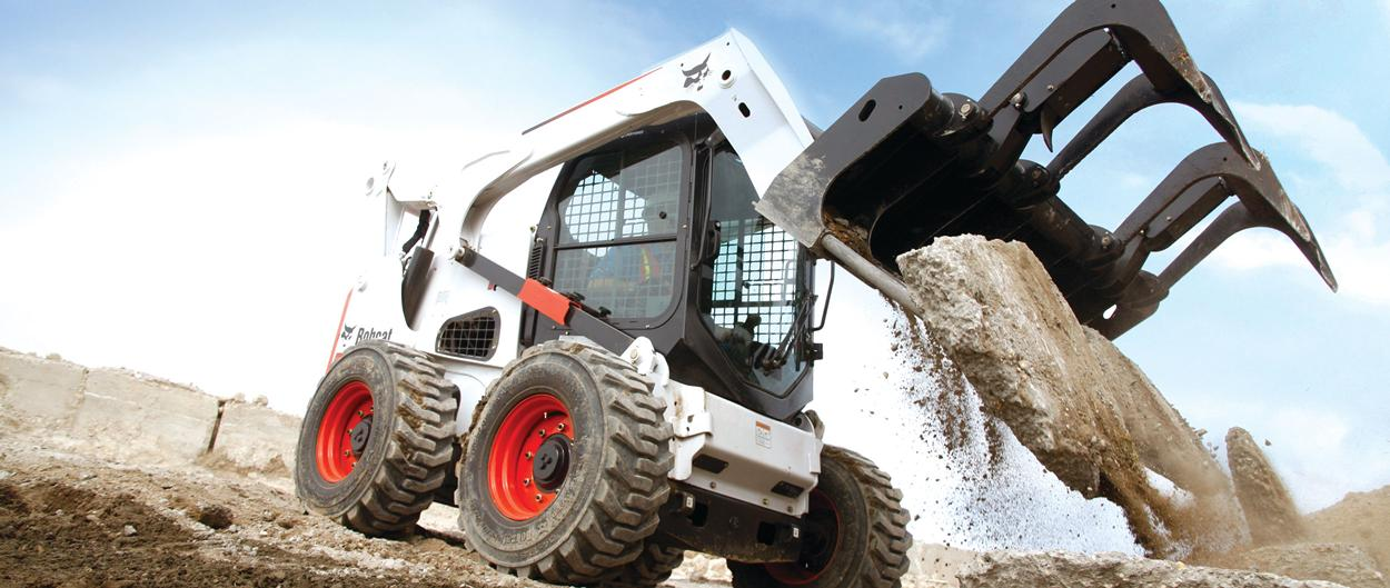Bobcat S850 skid-steer loader hauls debris with grapple attachment.