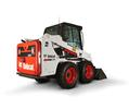 Bobcat S450 skid-steer loader lifting grass and soil.