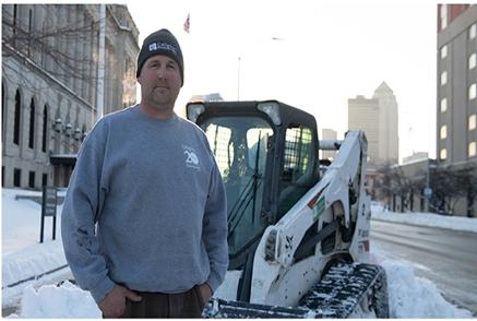Image Of Snow Removal Business Owner Posing In Front Of His Bobcat Compact Track Loader In The Snow