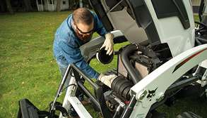 Homeowner Completing Routine Service On Bobcat Compact Tractor