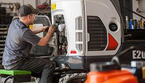 A Service Technician Inspects The Engine Compartment On An E20 Compact Excavator.