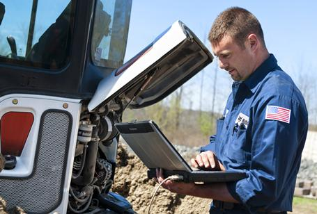 Bobcat mobile service technician diagnosing machine with laptop.