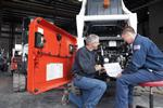 Bobcat service managers inspect the engine of a Skid-Steer Loader.