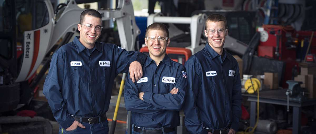 Group of three Bobcat service technicians in shop.