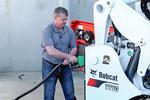 Operator filling a Bobcat T770 compact track loader with diesel fuel.