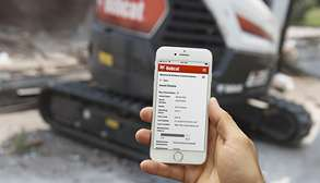 Hand Holding SmartPhone Showing Owner Portal Information With Bobcat Excavator In Background
