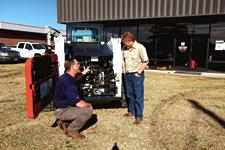 Bobcat dealer shows a customer the engine compartment of a Bobcat compact loader.