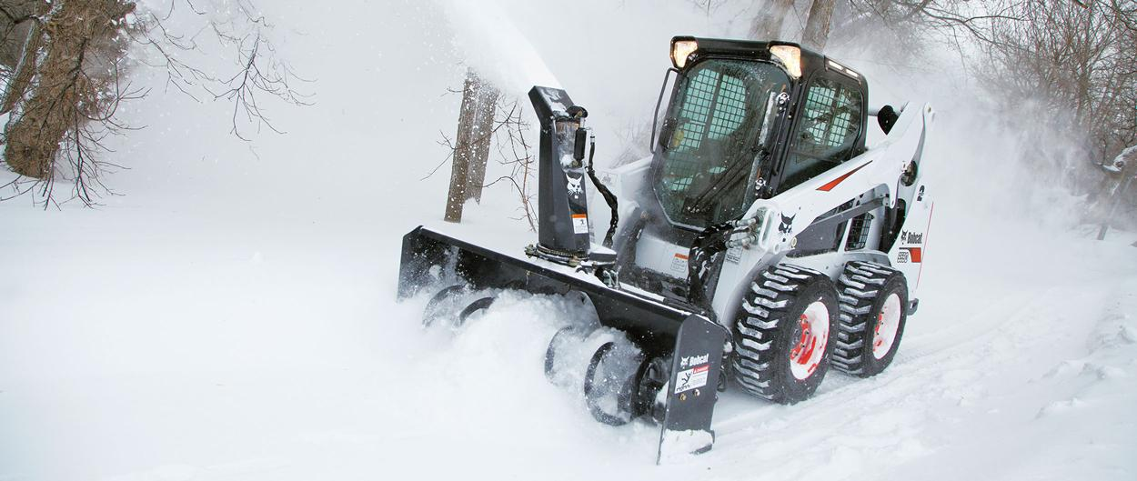 Bobcat S590 skid-steer loader with snow blower attachment in a snowy field.