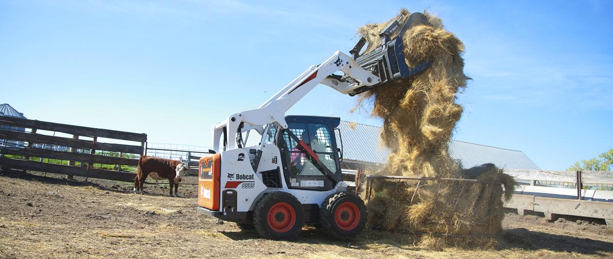 Bobcat S595 skid-steer loader and grapple attachment filling a cattle feeder with hay.