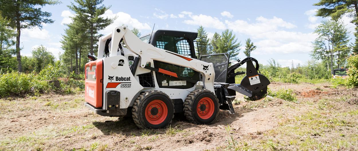 Bobcat S595 skid-steer loader and stump grinder attachment.